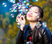 Young Asian Women Blowing Bubbles in the park — Stock Photo