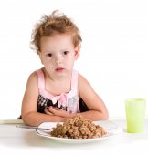 Dissatisfied girl with a big bowl of porridge — Stock Photo