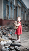 Neglected little girl with her teddy bear in the middle of demolished building. — Stock Photo