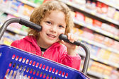 Little girl with shopping with a cart — Stock Photo