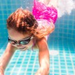 Girl smiles, swimming under water in the pool — Stock Photo #70227481