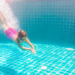 Girl smiles, swimming under water in the pool — Stock Photo #70227897