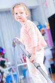 Küçük bir kız yere elektrikli süpürge ile temizlik — Stok fotoğraf