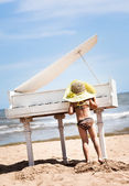 Little girl playing the piano at the beach. — Stock Photo