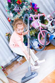 Little girl cleaning floor with vacuum cleaner — Stock Photo