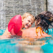 Happy family playing in blue water of swimming pool on a tropical resort at the sea — Stock Photo #71365983