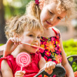 Two happy little girls with lollipops outdoors — Stock Photo #71987333