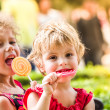 Two happy little girls with lollipops outdoors — Stock Photo #71987653