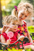 Two happy little girls with lollipops outdoors — Stock Photo