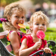 Two happy little girls with lollipops outdoors — Stock Photo #72690713