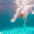 Girl smiles, swimming under water in the pool — Stock Photo #73667769