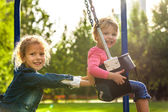 Two little sisters having fun on a swing — Stock Photo