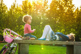 Funny little children sitting on bench — Stock Photo