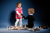 Two young ladies with shoes. Studio shot — Stock Photo