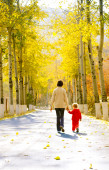 Mom and daughter walk in the rays of the autumn sun. — Stock Photo