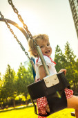 Pretty little girl on outdoor seesaw — Stock Photo