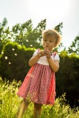 Happy child blowing dandelion outdoors in spring park — Stock Photo