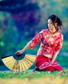 Portrait of a beautiful young asian woman with fan — Stock Photo