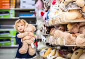 Pretty smiling little girl with teddy-bear in grocery store — Stock Photo
