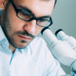 Young male doctor viewing through microscope — Stock Photo #75136461