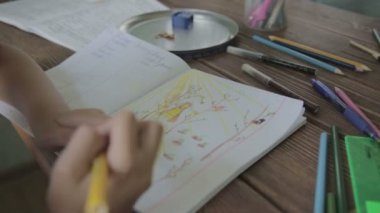 Girl drawing sun on notebook — Stock Video