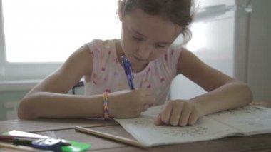 Flickan gör läxor för grundskolan. — Stockvideo
