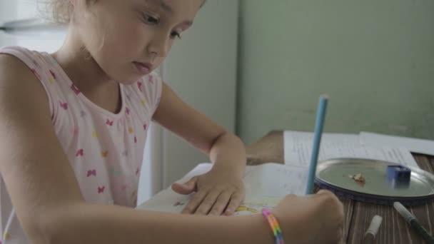 Chica está haciendo la tarea para la escuela primaria. — Vídeo de stock