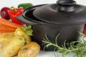 Fresh vegetables and herbs with cast iron pot — Stock Photo
