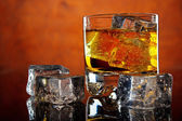 Glass of whiskey and ice cubes — Stock Photo