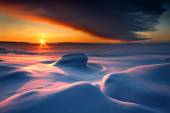 Snowy seascape with dark cloud and rising sun — Stock Photo