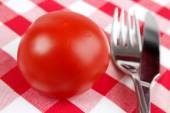 Tomato with dining utensils — Stock Photo