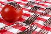 One tomato with many forks — Stock Photo
