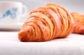 Croissant closeup on white tablecloth — Stock Photo