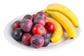 Plums and bananas on the plate — Stock Photo