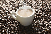 White espresso porcelain cup with coffee on roasted coffee beans background. — Zdjęcie stockowe