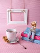 Cup of tea and a book on a pink background — Stock Photo