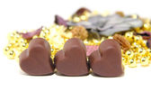 Three chocolate candy in the shape of heart on white background — Stock Photo