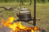 Teapot on naked flame outdoors — Stock Photo