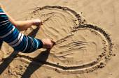 Heart drawing on sand a young pair — Stock Photo