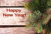 "Green fir-tree branch on a wooden background and a congratulation ""Happy New Year!"" — Stock fotografie"