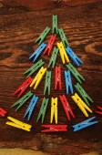 Christmas fir-tree from multi-colored clothespins on the made old wooden brown background — Stock Photo