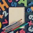 School supplies on a green table in an environment of color letters of the alphabet and numbers. Back to school background — Stock Photo #66401715