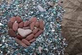 Pierres de couleur de mer en forme de cœur contre froissé papier noir — Photo