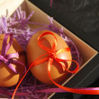 Two Easter eggs with bright tapes in square festive packing — Stock Photo #66611945