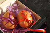 Two Easter eggs with bright tapes in square festive packing — Stock Photo