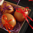 Three Easter eggs with bright tapes in square festive packing — Stock Photo #66637067