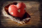 Red heart from a stone in a sink on a wooden surface with art processing under grunge — Stock Photo
