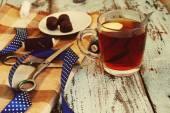 Scissors, threads, fabric, blue tape, cup of tea, candies — Foto de Stock