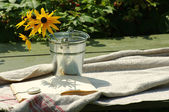 Yellow cultivated flowers in a metal bucket with the open book and a pocket watch on a linen cloth. Still life with the open book in a summer sunny day. — Stock Photo