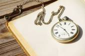 Old pocket watch and the open book with blank empty pages on a linen cloth — Stockfoto